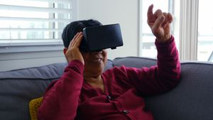 Senior woman using virtual reality headset in living room