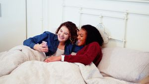 Lesbian couple using mobile phone on bed