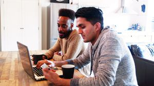 Gay couple using laptop while having coffee