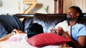 Gay couple relaxing together on couch