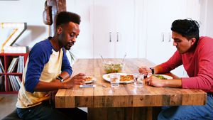 Gay couple interacting with each other while having meal