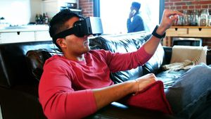 Man using virtual reality headset while friend talking on mobile phone