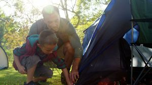 Father and son setting up a tent