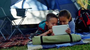 Siblings using digital tablet outside the tent at campsite