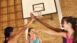 Group of high school kids giving high five in the basketball court