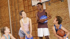 High school kids interacting with each other in basketball court