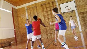 High school kids playing basketball in the court