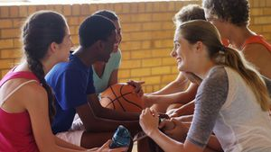 High school kids interacting while relaxing in the court