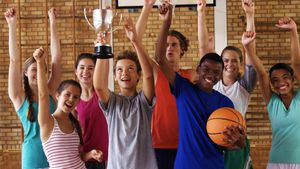 High school kids cheering while holding trophy in basketball court