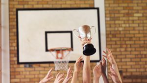 High school kids holding trophy in basketball court