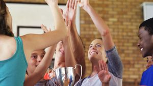 High school kids giving high five while holding trophy in basketball court