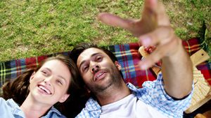 Couple interacting with each other while lying on picnic blanket