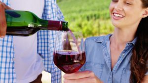 Man serving red wine to woman in the farm