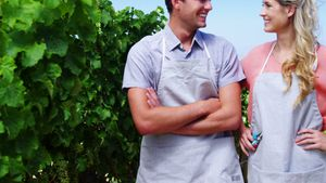 Happy couple standing in vineyard