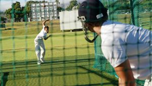 Cricket players practicing in the nets during a practice session