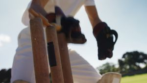 Wicket keeper collecting cricket ball behind stumps on cricket field