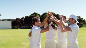 Cricket players giving high five during cricket match