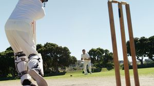 Batsman playing a defensive stroke during cricket match