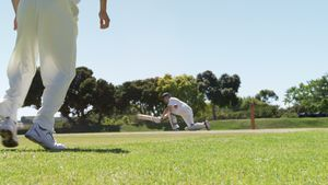 Batsman playing a sweep shot during cricket match