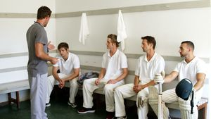 Coach interacting with cricket players