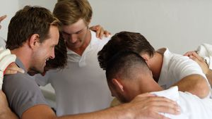 Cricket team forming a huddle in dressing room