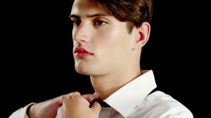 Androgynous man adjusting bow tie
