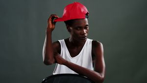 Androgynous man posing with red cap