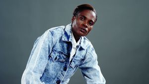 Androgynous man in denim jacket posing against grey background