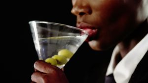 Androgynous man drinking cocktail against black background