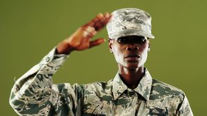 Androgynous man in camouflage uniform against green background