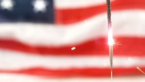 Sparkler burning against American flag background