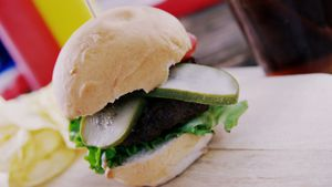 Hamburger and cold drink on wooden board