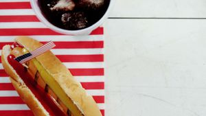 Hot dog and cold drink served on wooden table with 4th july theme