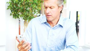 Businessman drinking cup of coffee and using mobile phone