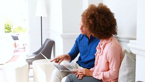 Smiling couple discussing over laptop