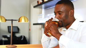 Man talking on mobile phone while having beer at counter