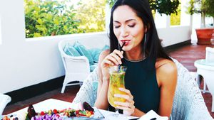 Beautiful woman drinking mocktail while having meal