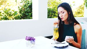 Beautiful woman using mobile phone while drinking mocktail