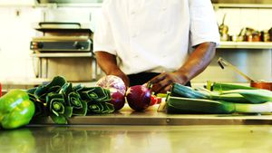 Chef cutting vegetables in commercial kitchen