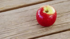 Red apple on wooden plank