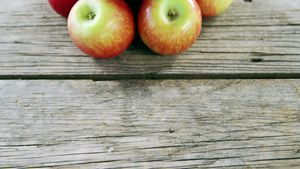 Red apples arranged on wooden plank