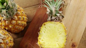 Overhead of halved pineapple on chopping board