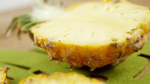 Halved pineapple on chopping board