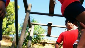 Kids climbing rope during obstacle course