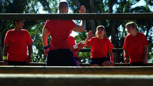 Trainer giving high five to kids in the boot camp