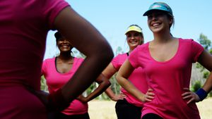 Female trainer assisting women while exercising in the boot camp