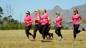 Female trainer assisting women running in the boot camp