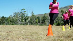 Group of women running through cones in the boot camp