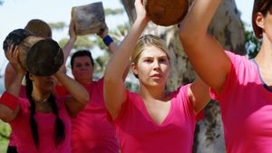 Group of women exercising with heavy log during obstacle course