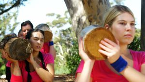 Group of women carrying heavy log during obstacle course